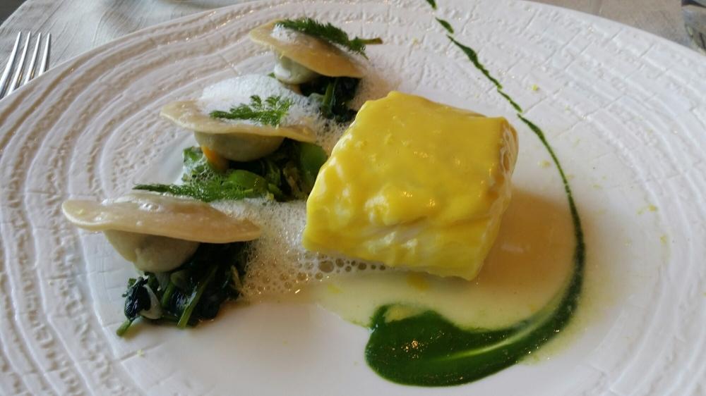 Pavé de merlu laqué beurre d'agrumes, raviole de champignons et cresson.